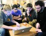 bloggers gather around laptop